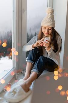 スタイリッシュな白いニットのセーター、スカーフ、帽子をかぶった若い魅力的な女性がクリスマスに窓辺に座ってガラスの雪玉プレゼントの装飾、冬の森の景色、ライトボケを保持しています