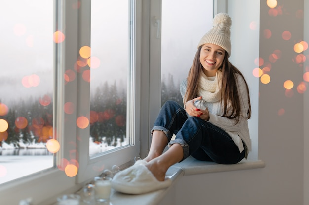 Молодая привлекательная женщина в стильном белом вязаном свитере, шарфе и шляпе сидит дома на подоконнике на рождество, держа в руках стеклянный снежный шар, настоящее украшение, вид на зимний лес, огни боке