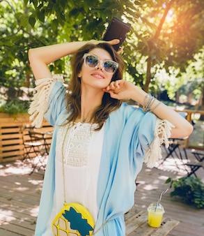 여름 패션 복장, 힙 스터 스타일, 흰 드레스, 파란색 케이프, 노란색 지갑, 선글라스, 웃고, 빈티지 사진 카메라, 세련된 액세서리, 트렌디 한 의류를 들고 젊은 매력적인 여자