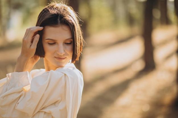 森の白いドレスの若い魅力的な女性