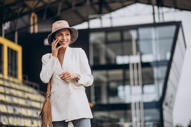 Молодая привлекательная женщина в белой куртке гуляет на открытом воздухе