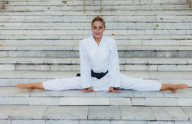 Молодая привлекательная женщина в белом кимоно с черным поясом. спортивная женщина, сидящая в шпагате на лестнице на открытом воздухе. боевые искусства