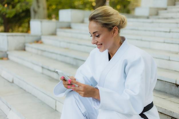 Молодая привлекательная женщина в белом кимоно с черным поясом. спортивная женщина сидит на лестнице и использует смартфон на открытом воздухе. отдых после тренировки. боевые искусства