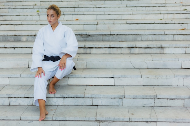Молодая привлекательная женщина в белом кимоно с черным поясом. спортивная женщина сидит на лестнице на открытом воздухе. боевые искусства