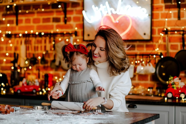 白い冬のセーターの若い魅力的な女性とドレスと赤い弓の小さな幼児の女の赤ちゃんがキッチンでクッキーを作っています。