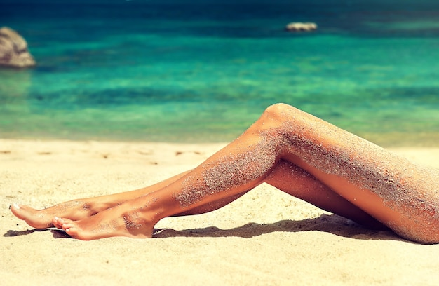 Молодая, привлекательная женщина лежит на пляже