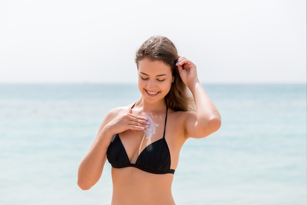 Young attractive woman is protecting her skin on the breast with sunblock at the sunny beach.