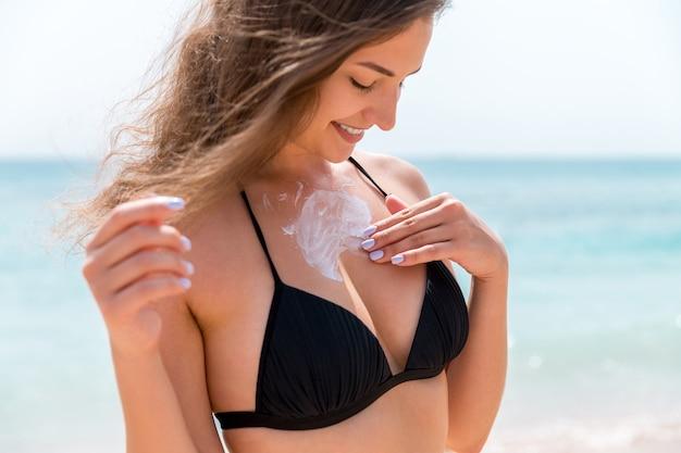 若い魅力的な女性は、太陽が降り注ぐビーチで日焼け止めで胸の肌を保護しています。