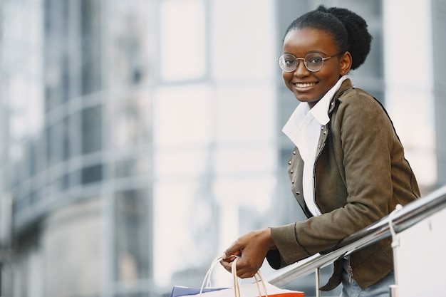 Young attractive woman in jacket and holding lot of shopping packages and walking along street. shopping concept