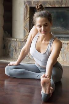 Young attractive woman in janu sirsasana pose