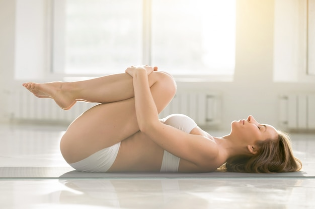 Young attractive woman in knees to chest pose, white background
