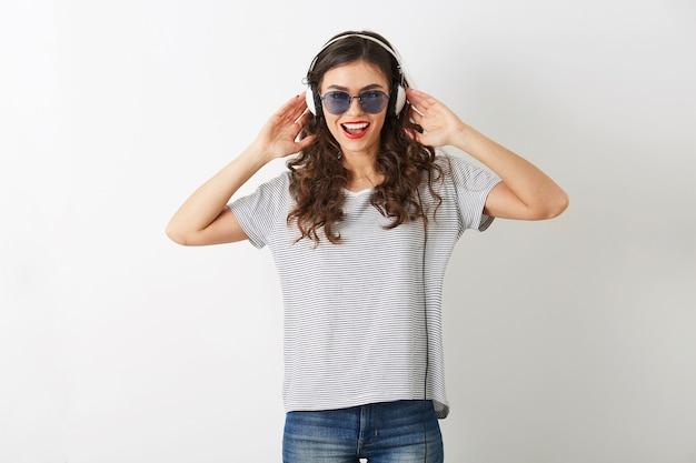 Giovane donna attraente ascoltando musica in cuffia, indossando occhiali da sole, isolati su sfondo bianco,