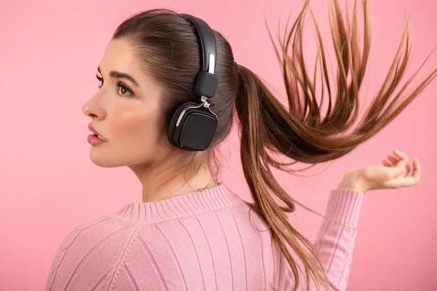 Young attractive woman listening to music in wireless headphones wearing pink sweater smiling happy positive mood posing on pink background isolated waving long hair tail