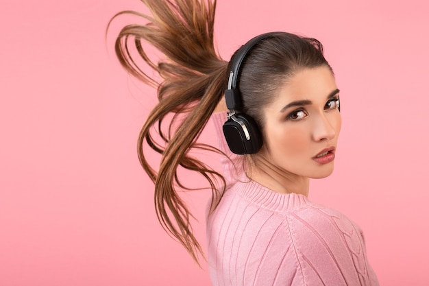 Young attractive woman listening to music in wireless headphones wearing pink sweater smiling happy positive mood posing on pink background