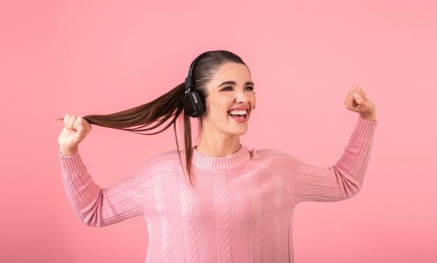 분홍색 스웨터를 입고 무선 헤드폰에서 음악을 듣고 젊은 매력적인 여자 분홍색 배경에 고립 된 재미 감정적 인 얼굴 표현에 포즈 행복 긍정적 인 분위기를 웃고