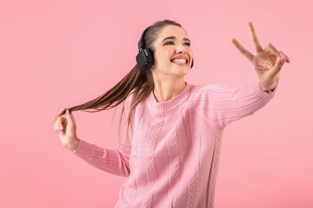 Молодая привлекательная женщина слушает музыку в беспроводных наушниках в розовом свитере улыбается