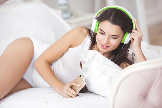 音楽を聴いている若い魅力的な女性。ヘッドフォンで魅力的な女の子。リラックスしたベッドで屋内の女性。イヤホンをつけている女性。