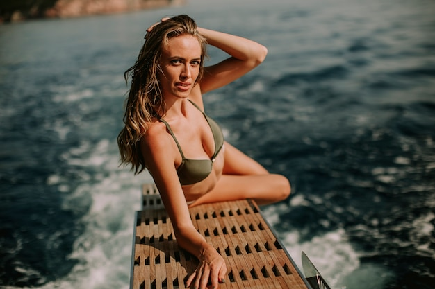 Young attractive woman on  luxury yacht floating at sea