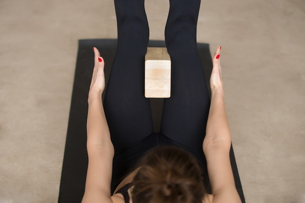 Young attractive woman lying in navasana pose with block, closeu