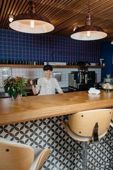 Молодая привлекательная женщина делает кофе в офисной столовой или на кухне