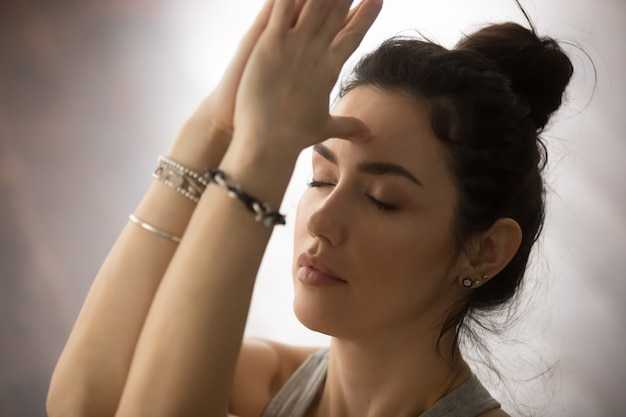 Young attractive woman making namaste with closed eyes