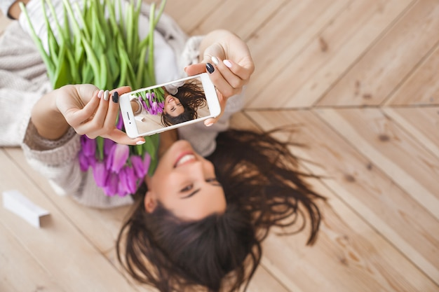 Young attractive woman making selfie with flowers indoors