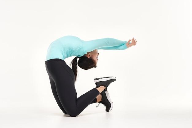 Молодая привлекательная женщина делает упражнения на растяжку йоги и гимнастики, изолированные на белом фоне