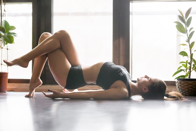 Young attractive woman in matsyasana pose, home interior backgro