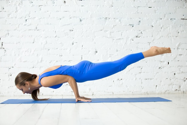 Young attractive woman in mayurasana pose, white studio backgrou