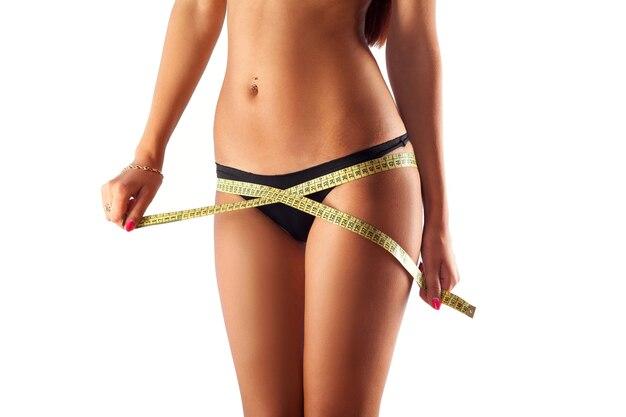 若い魅力的な女性は白い表面で彼女の体を測定します