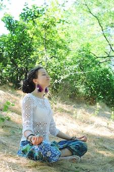 젊은 매력적인 여자는 가을 숲에 앉아 명상, 로터스 포즈