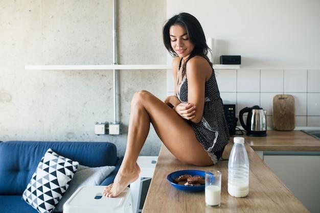 Giovane donna attraente al mattino in cucina, gambe lunghe sexy