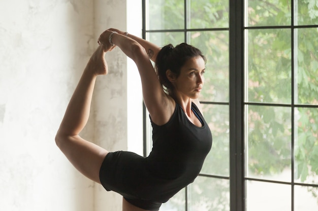 Young attractive woman in natarajasana pose, closeup