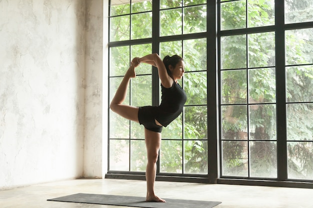 Young attractive woman in natarajasana pose, studio background