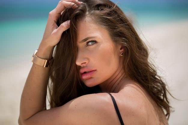 夏の日の海の近くの若い魅力的な女性