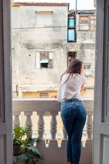 Young attractive woman on old balcony in apartments in havana