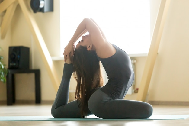 Young attractive woman in one legged king pigeon pose, home