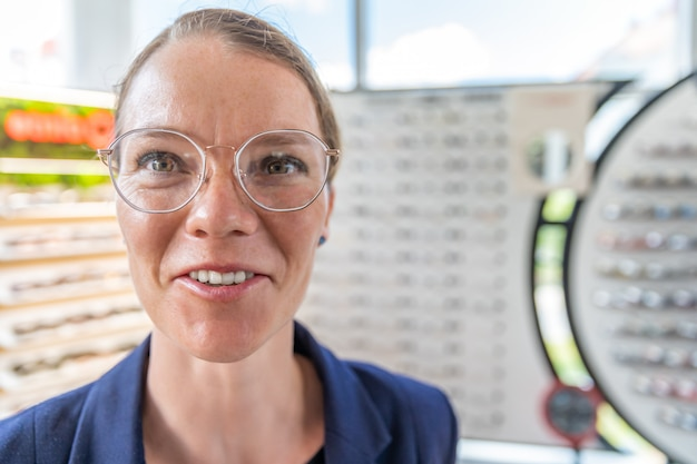 A young attractive woman in an optics store tries on new glasses