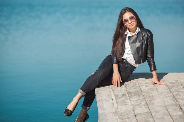 Young attractive woman outdoors. beautiful woman on a sea background in the fall time