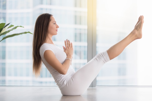 Young attractive woman in paripurna navasana pose against floor window