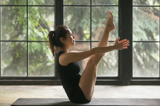 Young attractive woman in paripurna navasana pose