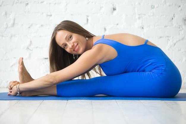 Young attractive woman in paschimottanasana pose, white studio b