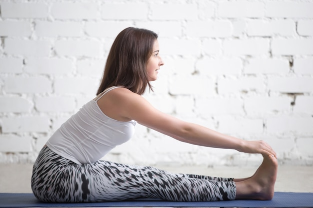 Young attractive woman in paschimottanasana pose, white studio