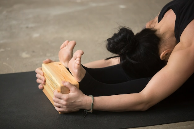 Young attractive woman in paschimottanasana pose with block, clo