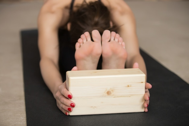 Young attractive woman in paschimottanasana pose with block, gre