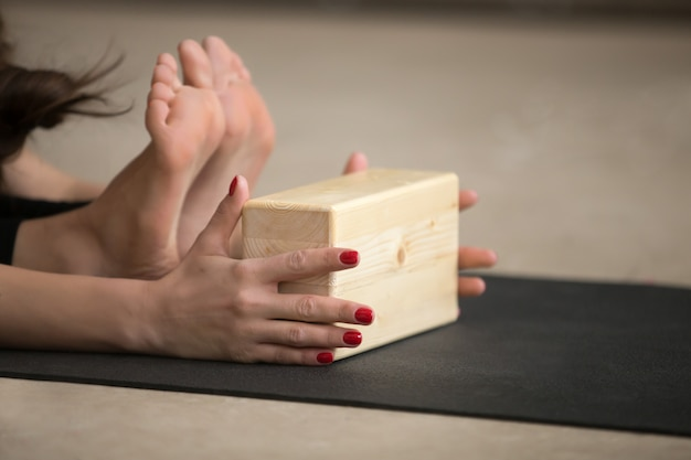 Young attractive woman in paschimottanasana pose with block, stu