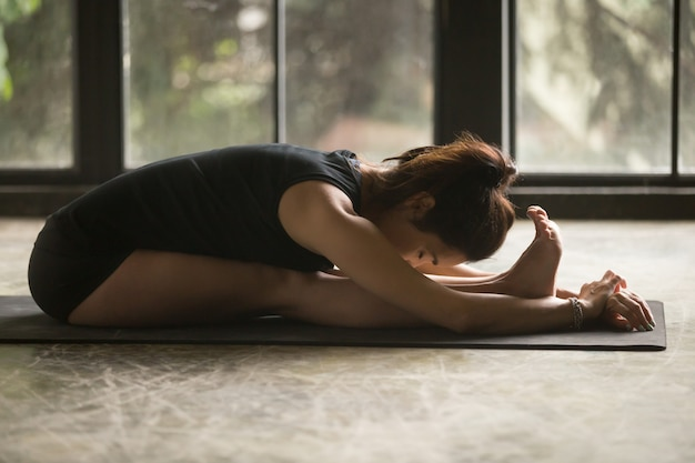 Young attractive woman in paschimottanasana pose
