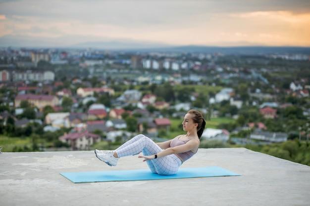 도시 배경에 체중 체력 훈련을 수행하는 젊은 매력적인 여자