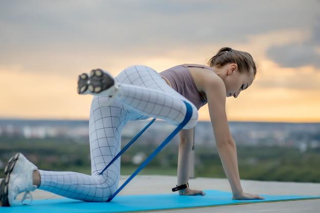 都市で体重フィットネストレーニングを実行する若い魅力的な女性