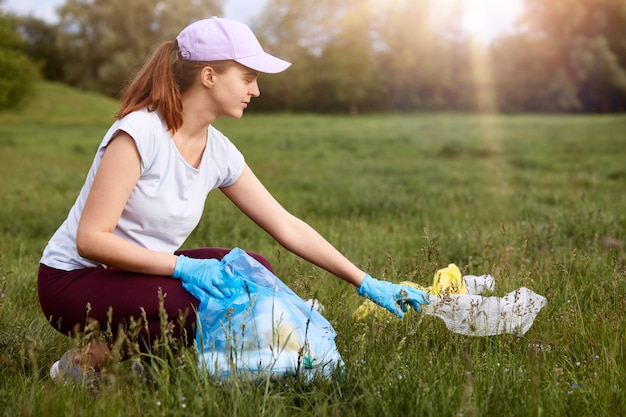 Young attractive woman picks up trash and puts it into bag on green meadow, environmental volunteer cleaning field and enjoying beautiful nature, solving environmental problems.